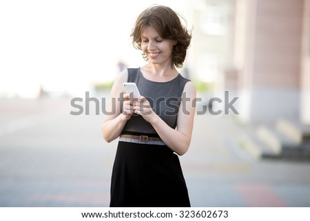 Portrait of happy beautiful woman holding cellphone in hands on the street in summer, using app, reading, sending or typing message with cheerful expression, friendly smiling - stock photo