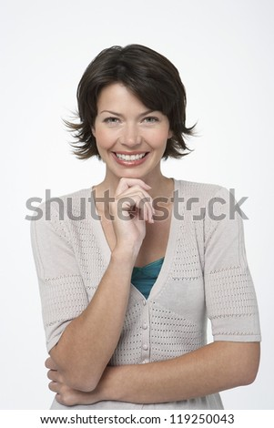 Portrait of happy beautiful woman with hand on chin isolated over white background - stock photo