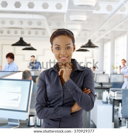 Portrait of happy black female office worker in office with working people. - stock photo