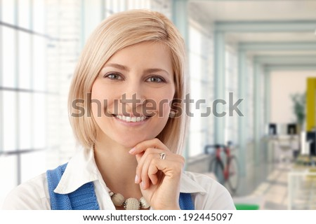 Portrait of happy blond female office worker smiling at workplace. - stock photo