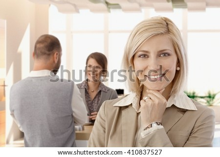 Portrait of happy bond businesswoman at office, looking at camera, smiling. - stock photo