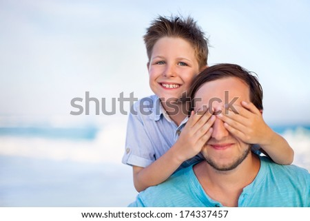Portrait of happy boy covering father's eyes at beach - stock photo