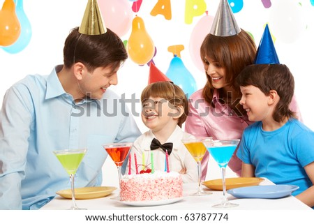 Portrait of happy boy having his birthday party with parents and elder brother near by - stock photo