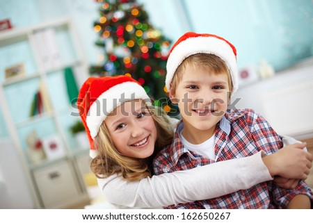 Portrait of happy boy in his sister embrace, both looking at camera on Christmas evening - stock photo