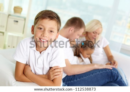 Portrait of happy boy on background of his parents and sister - stock photo