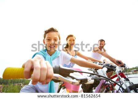 Portrait of happy boy on bike with his parents - stock photo