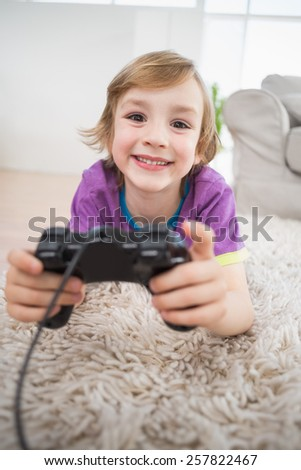 Portrait of happy boy playing video game while lying on rug at home - stock photo