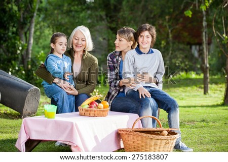 Portrait of happy boy sitting with family at campsite - stock photo