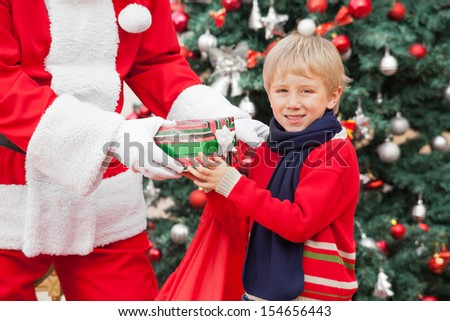 Portrait of happy boy taking present from Santa Claus against Christmas tree - stock photo