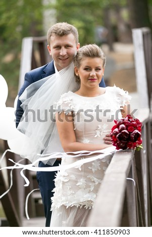 Portrait of happy bride and groom on wooden bridge at windy day - stock photo