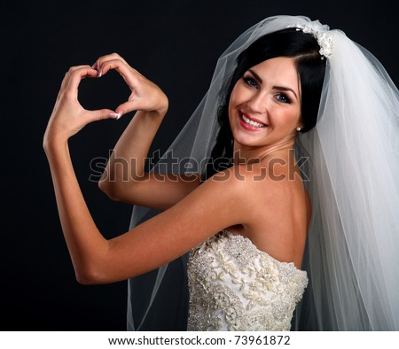 Portrait of happy bride in beautiful dress making shape of heart with her hands on black background - stock photo
