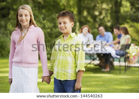 Portrait of happy brother and sister holding hands with family having lunch in background - stock photo