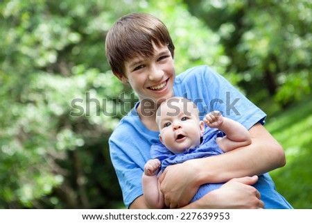 Portrait of happy brother and sisters in summer park - stock photo