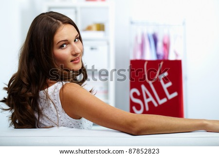 Portrait of happy brunette looking at camera with sale bag on background - stock photo