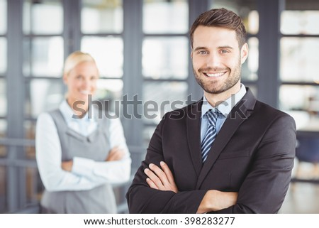 Portrait of happy businesman with arms crossed while female colleague in background - stock photo