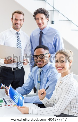 Portrait of happy business colleagues reviewing a report at desk in office - stock photo