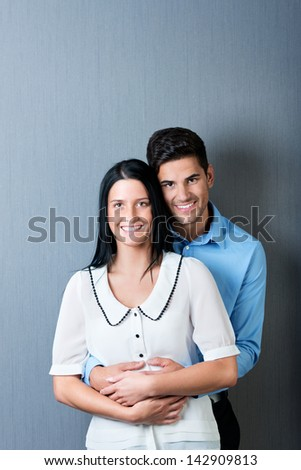 Portrait of happy business couple against blue wall - stock photo