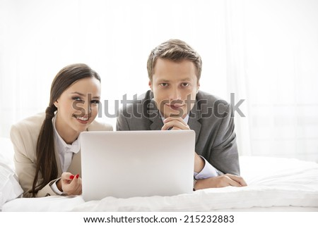 Portrait of happy business couple with laptop in hotel - stock photo