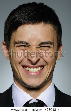 Portrait of HAPPY business man in formal suit and black tie . expressions on gray background - stock photo
