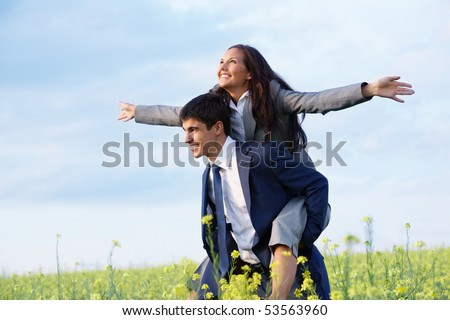 Portrait of happy business partners enjoying life and freedom in meadow - stock photo