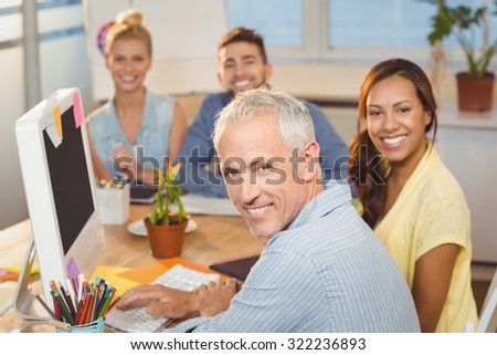 Portrait of happy business people sitting by desk with computer in creative office - stock photo