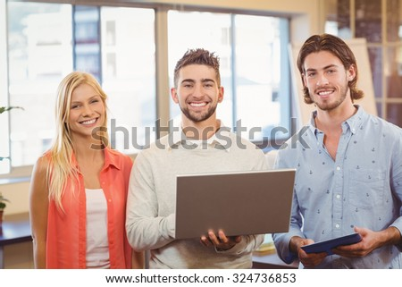 Portrait of happy business people using laptop in creative office - stock photo