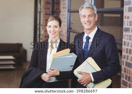 Portrait of happy business people with files standing by window at office - stock photo
