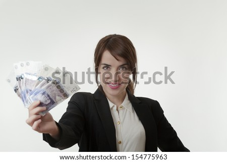 Portrait of happy business woman holding fanned english banknotes - stock photo