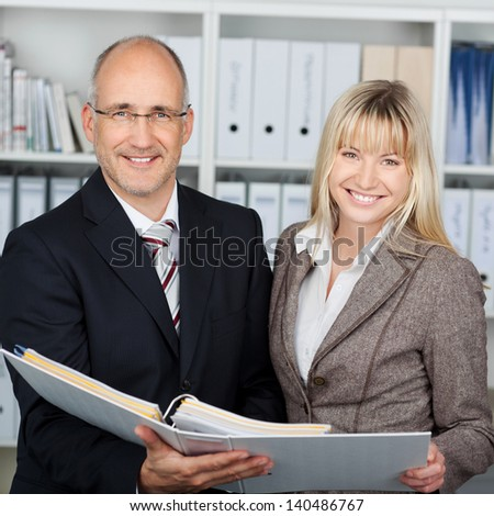 Portrait of happy businessman and businesswoman holding binder - stock photo