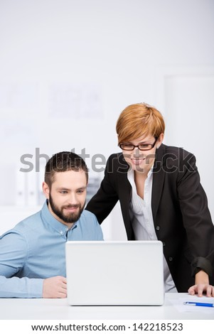 Portrait of happy businessman and businesswoman with laptop at office desk - stock photo