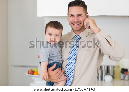 Portrait of happy businessman carrying baby boy while while using cellphone at home - stock photo