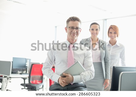 Portrait of happy businessman holding tablet PC with female colleagues in background at office - stock photo