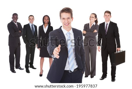 Portrait of happy businessman offering handshake with team standing against white background - stock photo