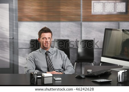 Portrait of happy businessman sitting at office desk, looking at camera, smiling. - stock photo