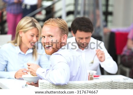 Portrait of happy businessman sitting with colleagues at outdoor restaurant - stock photo