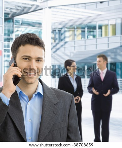 Portrait of happy businessman talking on mobile in office lobby. - stock photo