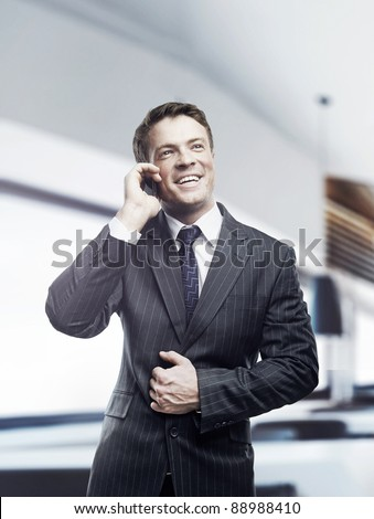 Portrait of happy businessman talking on mobile standing in office, smiling. - stock photo