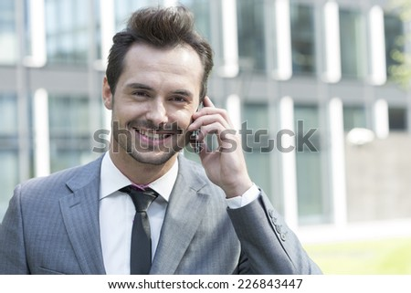 Portrait of happy businessman using cell phone outside office - stock photo