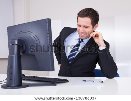 Portrait Of Happy Businessman Using Computer At Workplace - stock photo