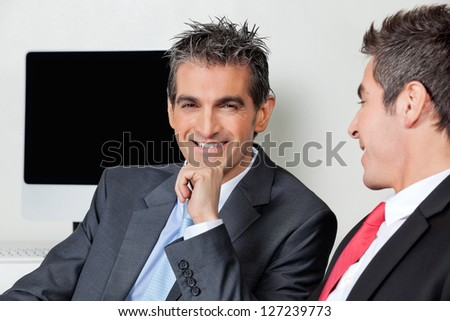 Portrait of happy businessman with colleague at office - stock photo