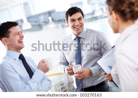 Portrait of happy businessmen with cups laughing - stock photo