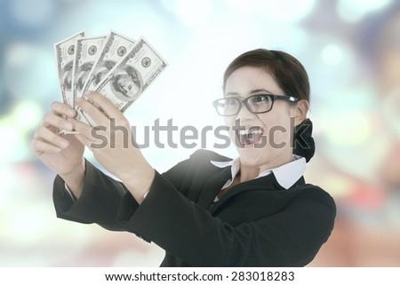 Portrait of happy businesswoman holding money dollars, shot against bokeh background - stock photo