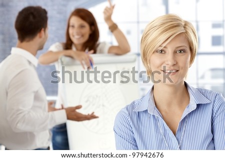 Portrait of happy businesswoman in meeting room, with colleagues at whiteboard, selective focus. - stock photo