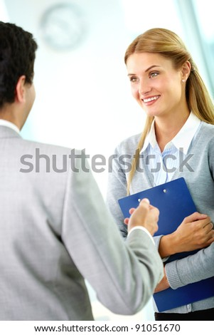Portrait of happy businesswoman looking at her partner while interacting with him - stock photo