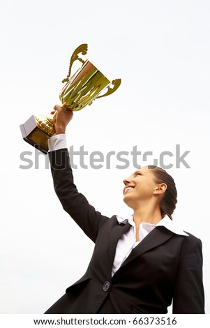 Portrait of happy businesswoman raising championship cup - stock photo