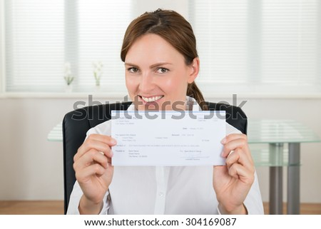 Portrait Of Happy Businesswoman Showing Cheque In Office - stock photo