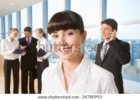 Portrait of happy businesswoman smiling at camera on background of working employees - stock photo
