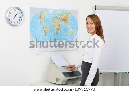 Portrait of happy businesswoman using copy machine in office - stock photo