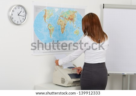 Portrait of happy businesswoman using fax machine in office - stock photo