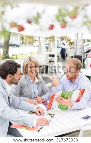 Portrait of happy businesswoman with male colleagues deciding menu at sidewalk cafe - stock photo
